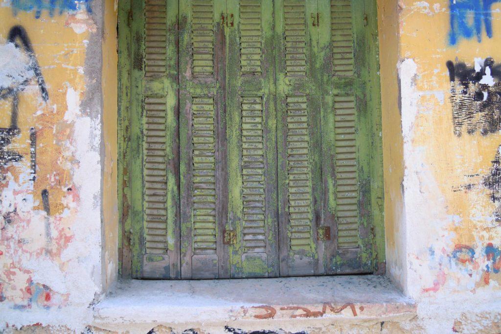 Grön färg som flagnar på fönsterluckor